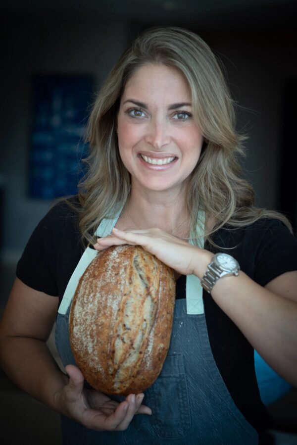 Chef Edna Cochez holding a loaf of fresh baked bread, wearing a black short sleeve top and her chef's apron, smiling